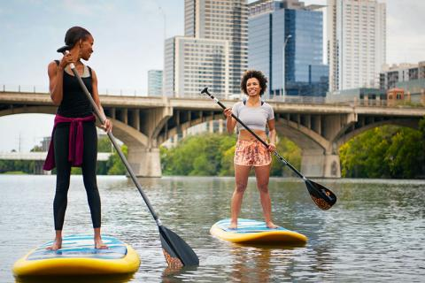 Visit Austin, two women stand up paddleboarding